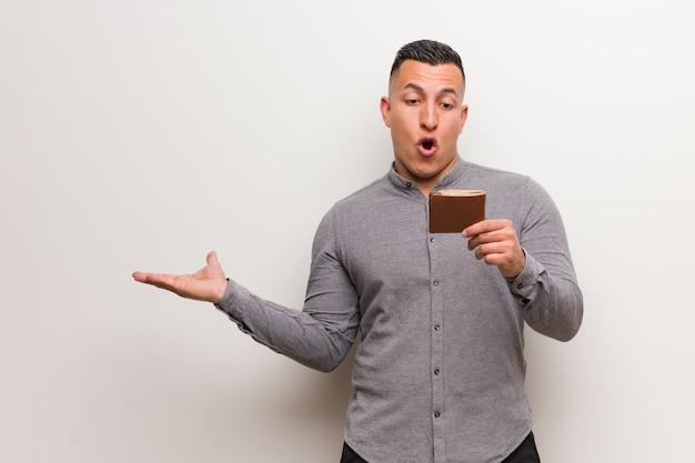 Jovem latina segurando uma carteira segurando algo na mão de palma