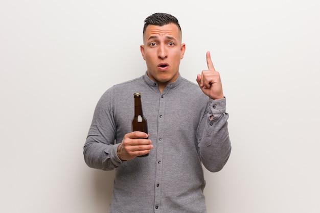 Jovem latina, segurando uma cerveja, tendo uma ótima idéia