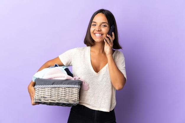 Jovem latina segurando uma cesta de roupas