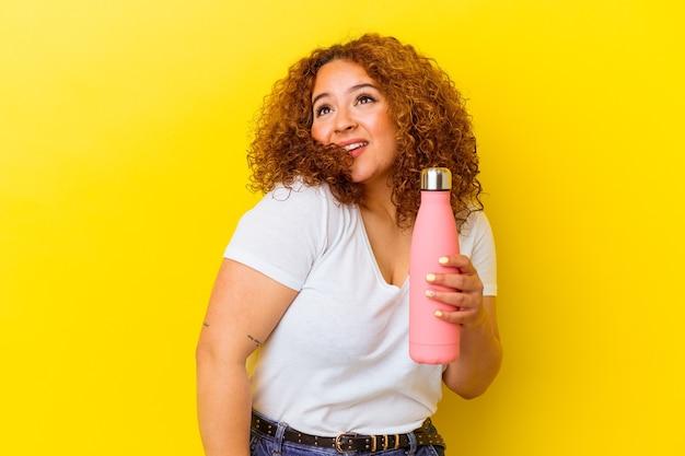 Jovem latina segurando uma garrafa térmica isolada em um fundo amarelo, sonhando em alcançar objetivos e propósitos