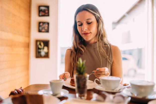 Jovem latina sentada em um café comendo bolo