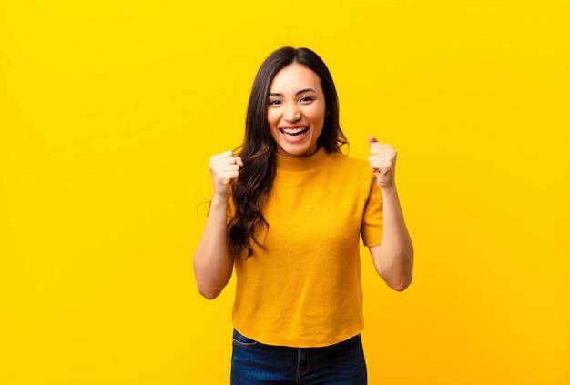 Jovem latina, sentindo-se chocado, animado e feliz, rindo e comemorando o sucesso, dizendo uau! na parede plana