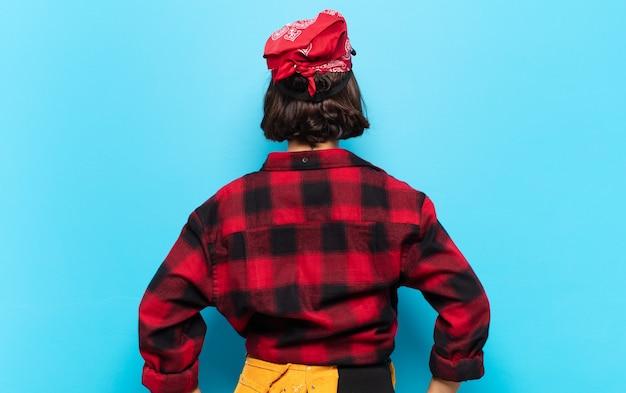 Jovem latina sentindo-se confusa ou cheia ou dúvidas e perguntas, imaginando, com as mãos na cintura, retrovisor