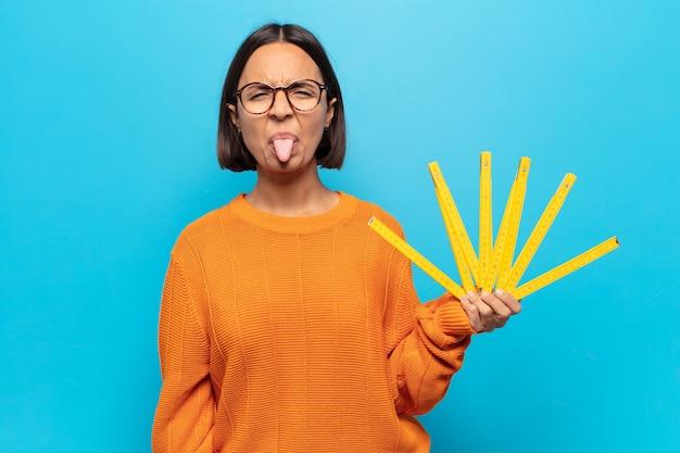 Jovem latina sentindo-se enojada e irritada, mostrando a língua, não gostando de algo nojento e nojento