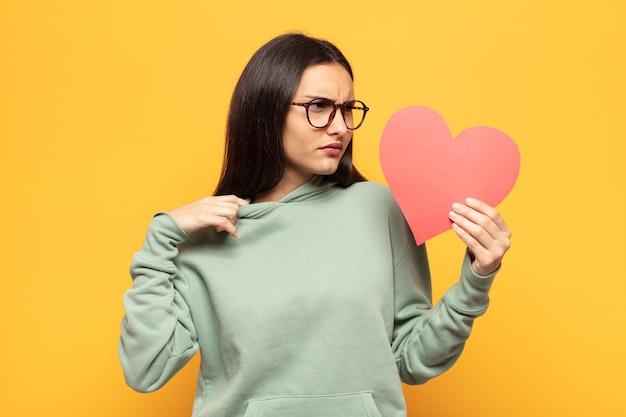 Jovem latina sentindo-se estressada, ansiosa, mostrando um coração vermelho