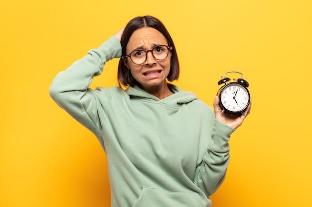 Jovem latina sentindo-se estressada, preocupada, ansiosa ou assustada, com as mãos na cabeça, entrando em pânico com o erro