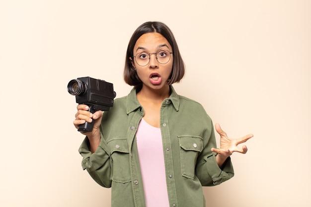 Jovem latina sentindo-se extremamente chocada e surpresa, ansiosa e em pânico, com um olhar estressado e horrorizado