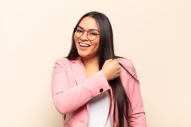 Jovem latina sentindo-se feliz, positiva e bem-sucedida, motivada para enfrentar um desafio ou comemorar bons resultados