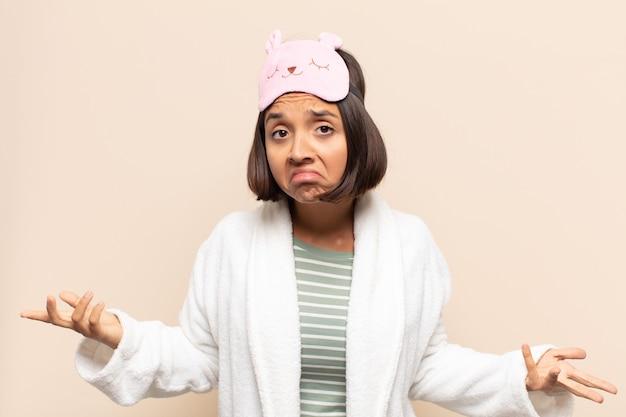 Jovem latina sentindo-se sem noção e confusa, sem fazer ideia, absolutamente perplexa com um olhar idiota ou tolo