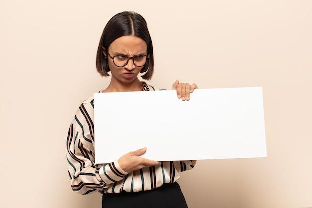 Jovem latina sentindo-se triste, chateada ou com raiva e olhando para o lado com uma atitude negativa, franzindo a testa em desacordo