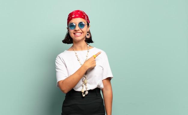 Jovem latina sorrindo alegremente, sentindo-se feliz e apontando para o lado e para cima, mostrando o objeto no espaço da cópia