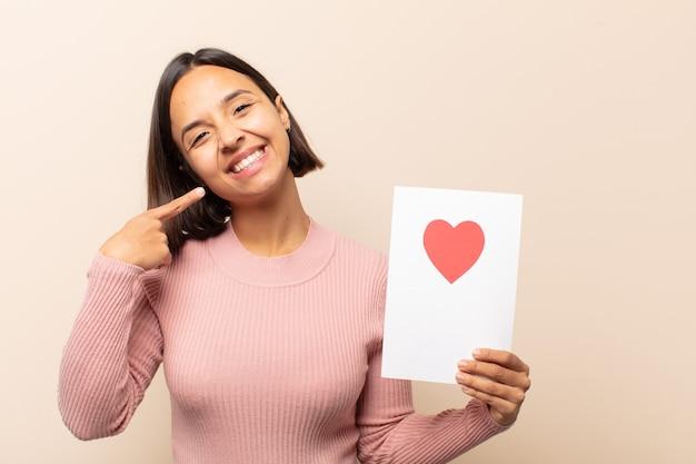 Jovem latina sorrindo com confiança apontando para o próprio sorriso largo, atitude positiva, relaxada e satisfeita