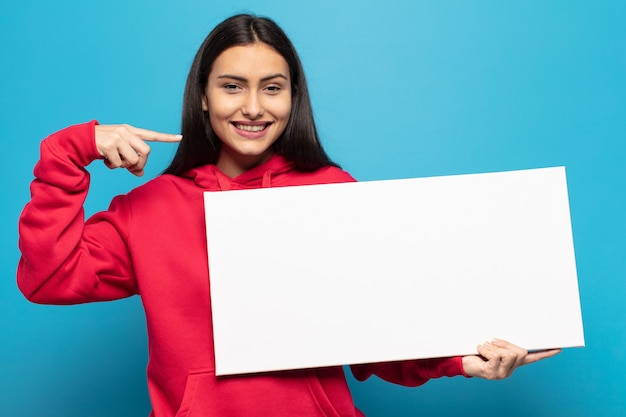 Jovem latina sorrindo com confiança apontando para o próprio sorriso largo, positivo