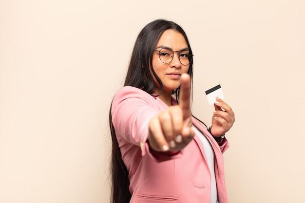 Jovem latina sorrindo com orgulho e confiança fazendo a pose número um triunfantemente, sentindo-se uma líder