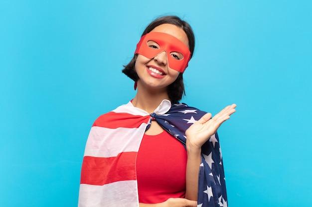 Jovem latina sorrindo com orgulho e confiança, sentindo-se feliz e satisfeita e mostrando um conceito no espaço da cópia