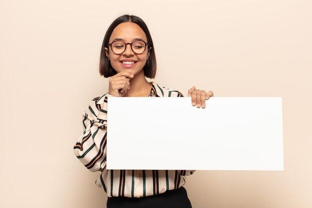 Jovem latina sorrindo com uma expressão feliz e confiante com a mão no queixo