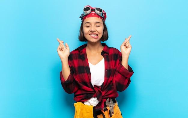 Jovem latina sorrindo e cruzando os dedos ansiosamente, preocupada e desejando ou esperando por boa sorte