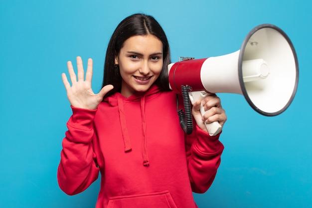 Jovem latina sorrindo e parecendo amigável, mostrando o número cinco ou quinto com a mão para a frente, em contagem regressiva