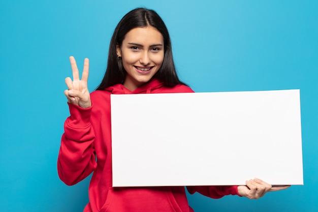 Jovem latina sorrindo e parecendo amigável, mostrando o número dois ou o segundo com a mão para a frente, em contagem regressiva