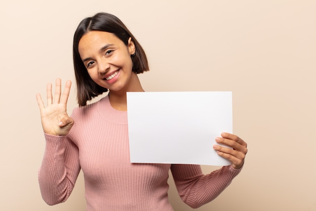 Jovem latina sorrindo e parecendo amigável, mostrando o número quatro ou o quarto com a mão para a frente, em contagem regressiva