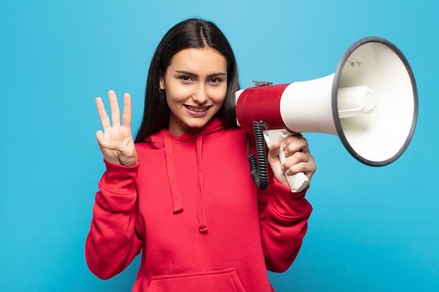 Jovem latina sorrindo e parecendo amigável, mostrando o número três ou terceiro com a mão para a frente, em contagem regressiva