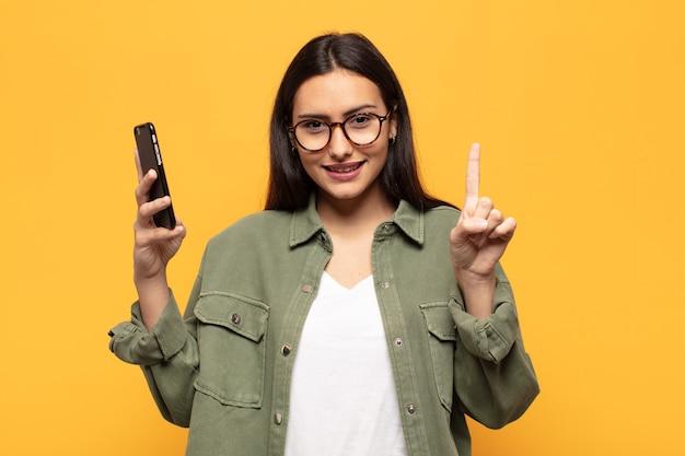 Jovem latina sorrindo e parecendo amigável, mostrando o número um ou primeiro com a mão para a frente, em contagem regressiva Foto Premium