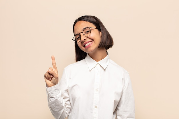 Jovem latina sorrindo e parecendo amigável, mostrando o número um ou primeiro com a mão para a frente, em contagem regressiva