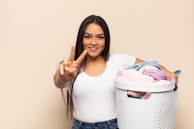 Jovem latina sorrindo e parecendo feliz, despreocupada e positiva, gesticulando vitória ou paz com uma mão