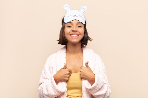 Jovem latina sorrindo, parecendo feliz, positiva, confiante e bem-sucedida, com os dois polegares para cima