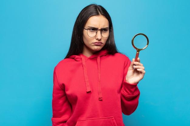 Jovem latina triste, chateada ou com raiva e olhando para o lado com uma atitude negativa, franzindo a testa em desacordo