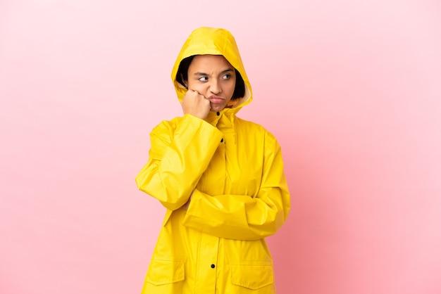 Jovem latina vestindo um casaco à prova de chuva sobre um fundo isolado com uma expressão de cansaço e tédio