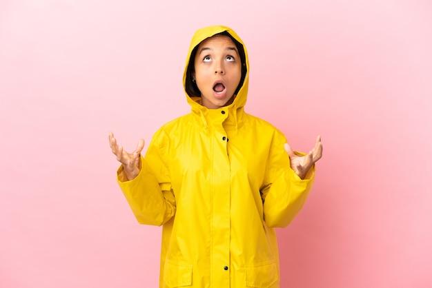 Jovem latina vestindo um casaco à prova de chuva sobre um fundo isolado estressada sobrecarregada