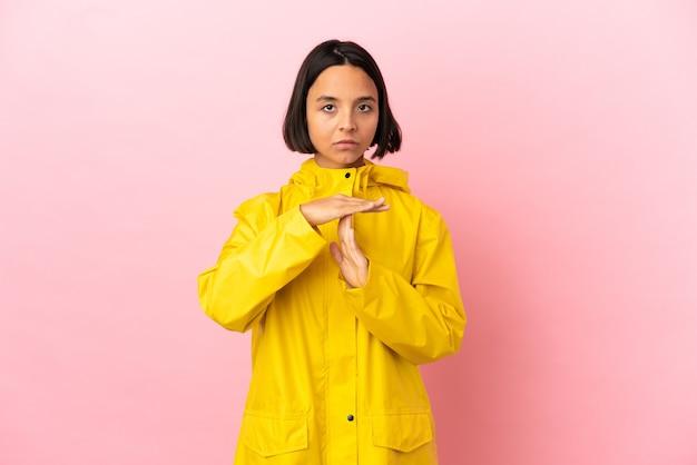 Jovem latina vestindo um casaco à prova de chuva sobre um fundo isolado fazendo gesto de castigo