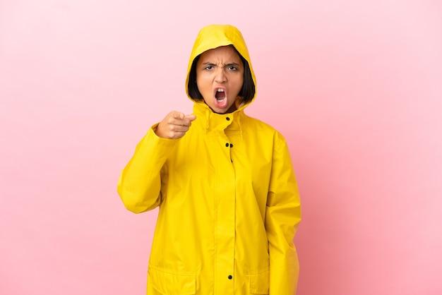Jovem latina vestindo um casaco à prova de chuva sobre um fundo isolado frustrada e apontando para a frente