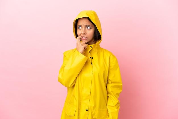 Jovem latina vestindo um casaco à prova de chuva sobre um fundo isolado, nervosa e assustada