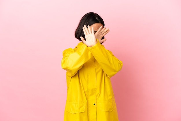 Jovem latina vestindo um casaco à prova de chuva sobre um fundo isolado nervosa esticando as mãos para a frente
