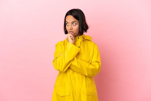 Jovem latina vestindo um casaco à prova de chuva sobre um fundo isolado, tendo dúvidas enquanto olha para cima