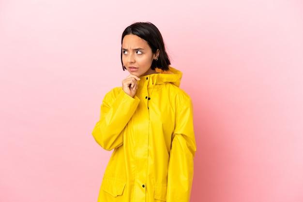 Jovem latina vestindo um casaco à prova de chuva sobre um fundo isolado, tendo dúvidas