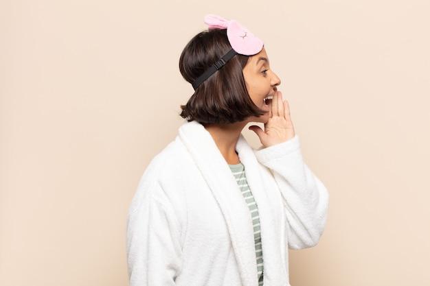 Jovem latina vista de perfil, parecendo feliz e animada, gritando e chamando para copiar o espaço ao lado