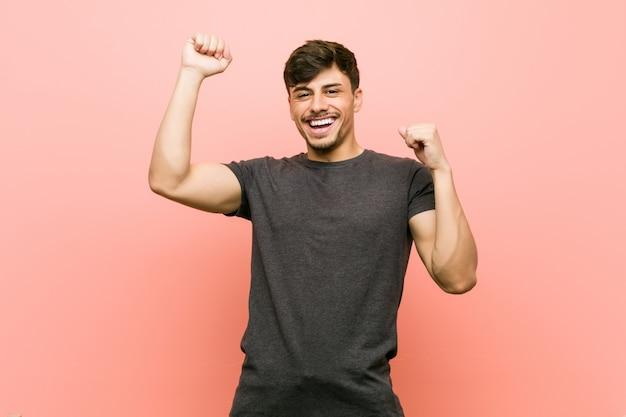 Jovem latino-americano casual comemorando um dia especial, pula e levanta os braços com energia.