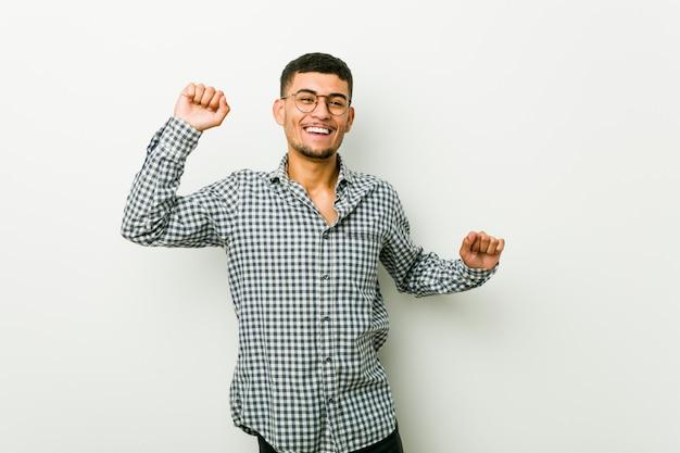 Jovem latino-americano, comemorando um dia especial, pula e levanta os braços com energia.