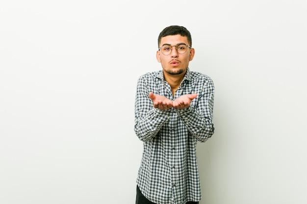 Jovem latino-americano, dobrar os lábios e segurando as palmas das mãos para enviar beijo de ar.