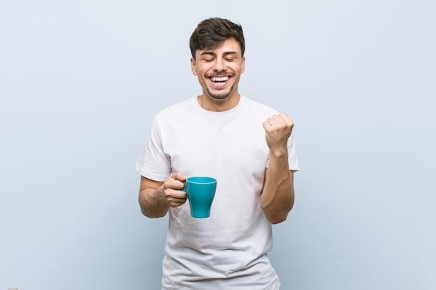 Jovem latino-americano, segurando um copo torcendo despreocupado e animado. conceito de vitória