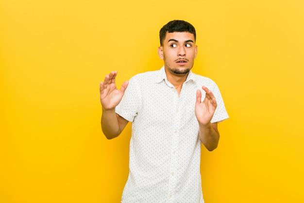 Jovem latino-americano sendo chocado devido a um perigo iminente