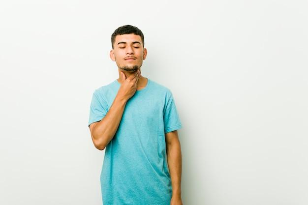 Jovem latino-americano sofre de dor na garganta devido a um vírus ou infecção.