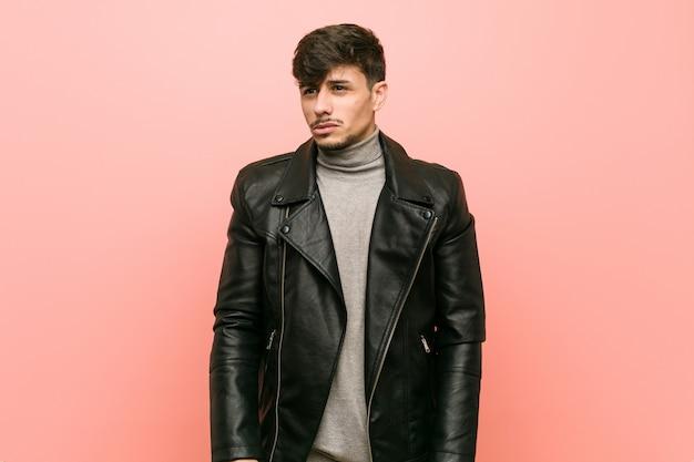 Jovem latino-americano, vestindo uma jaqueta de couro confusa, sente-se duvidoso e inseguro.