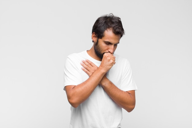 Jovem latino bonito, doente, com dor de garganta e sintomas de gripe, tosse com a boca coberta