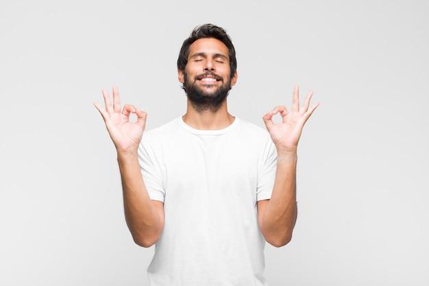 Jovem latino bonito parecendo concentrado e meditando, sentindo-se satisfeito e relaxado, pensando ou fazendo uma escolha