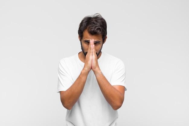 Jovem latino bonito se sentindo preocupado, esperançoso e religioso, orando fielmente com as palmas das mãos pressionadas, implorando perdão