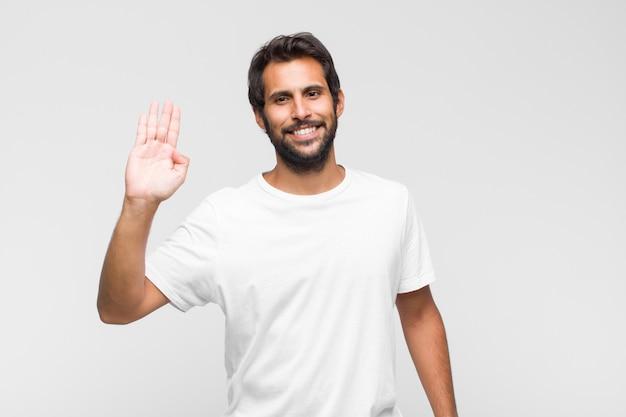 Jovem latino bonito sorrindo feliz e alegre, acenando com a mão, dando as boas-vindas e cumprimentando você ou dizendo adeus